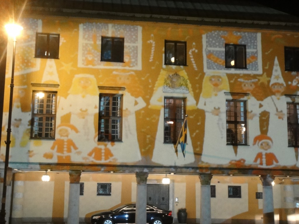 painting of Swedish St Lucia procession shown on building facade in Warsaw through projection mapping or video mapping